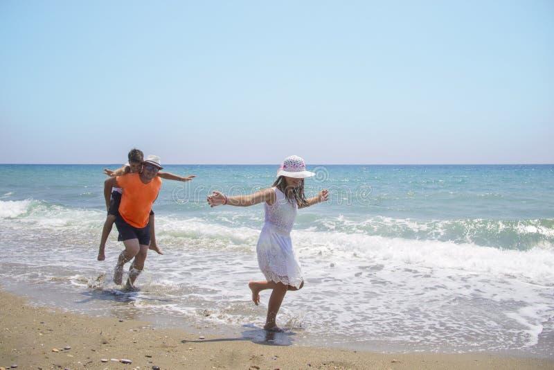 Engendre con los niños que se divierten en la playa en el tiempo del día imagen de archivo libre de regalías