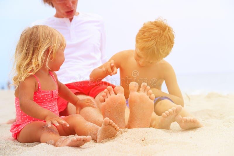 Engendre con los pies del hijo y de la hija en la playa de la arena foto de archivo