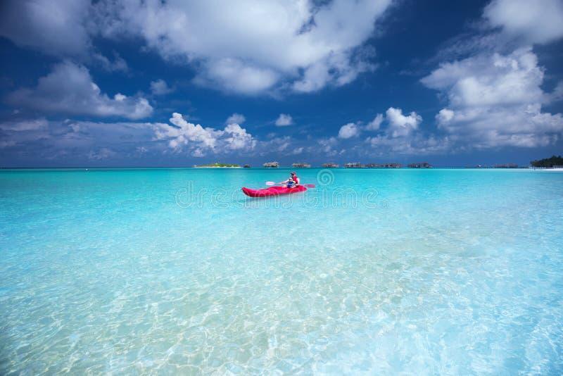 Engendre con su hijo kayaking en laguna verde en la isla tropical imágenes de archivo libres de regalías