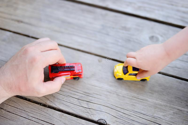 Engendre con su pequeño hijo que juega con los coches del juguete imagen de archivo