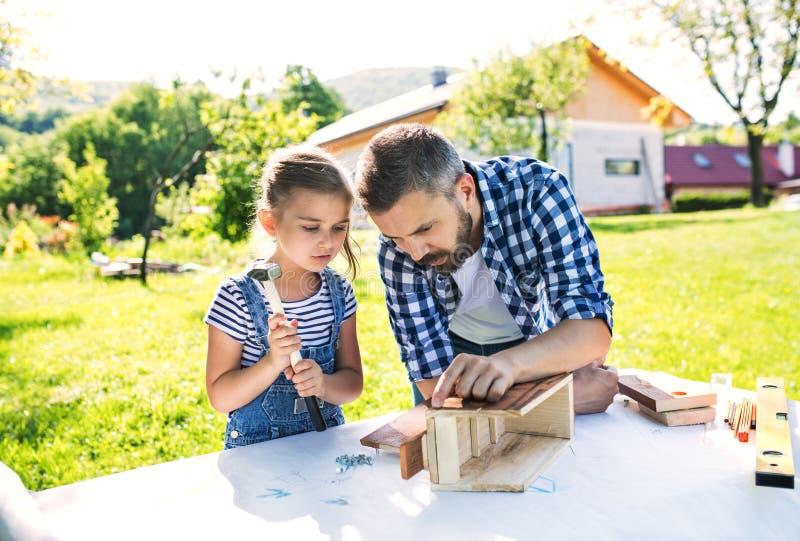 Engendre con una pequeña hija afuera, haciendo la pajarera de madera foto de archivo