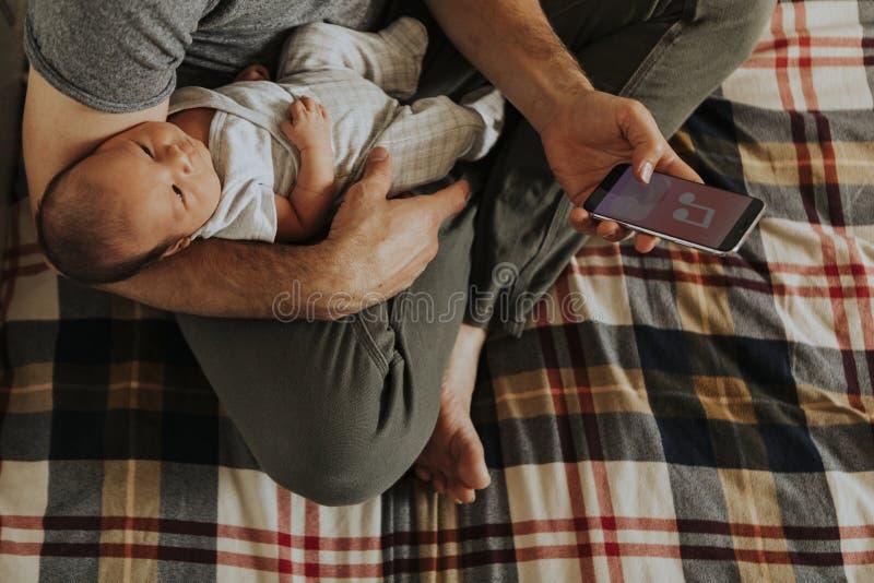 Engendre detener a su bebé mientras que usa su teléfono fotografía de archivo