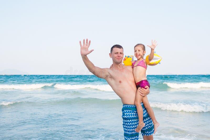 Engendre detener a un beb? alto con la cara feliz cerca del mar imagenes de archivo