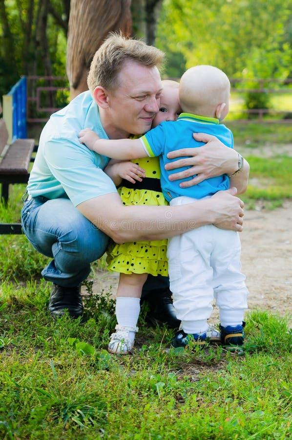 Engendre el abrazo de la pequeña hija en vestido e hijo amarillos en camisa azul fotos de archivo