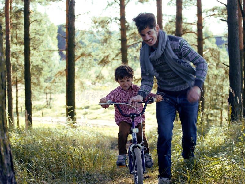Engendre el aprendizaje de su hijo para montar en la bicicleta afuera, familia feliz real en naturaleza enjoing del bosque del ve fotografía de archivo libre de regalías