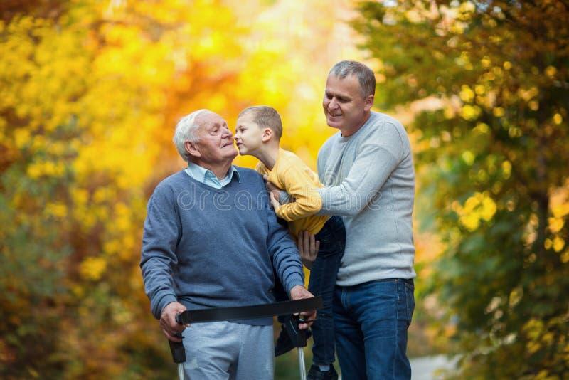 Engendre el hijo y al nieto adultos hacia fuera para un paseo en el parque imagen de archivo