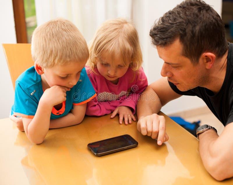 Engendre el hijo y a la muchacha que comprueban el teléfono elegante fotografía de archivo libre de regalías