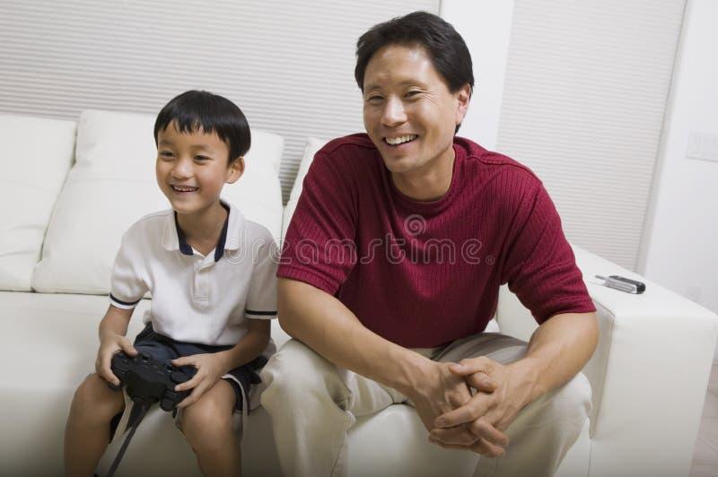 Engendre el videojuego de observación del juego del hijo en vista delantera del sofá imágenes de archivo libres de regalías