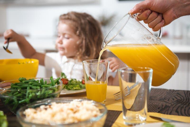 Engendre el zumo de naranja de colada en el vidrio para la niña imagen de archivo libre de regalías