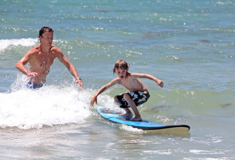 Engendre enseñando a su hijo joven a cómo practicar surf fotografía de archivo