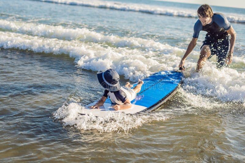 Engendre enseñando a su hijo joven a cómo practicar surf en el mar el vacaciones fotos de archivo