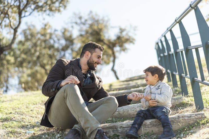 Engendre jugar con el hijo en escaleras del parque del aire libre fotografía de archivo