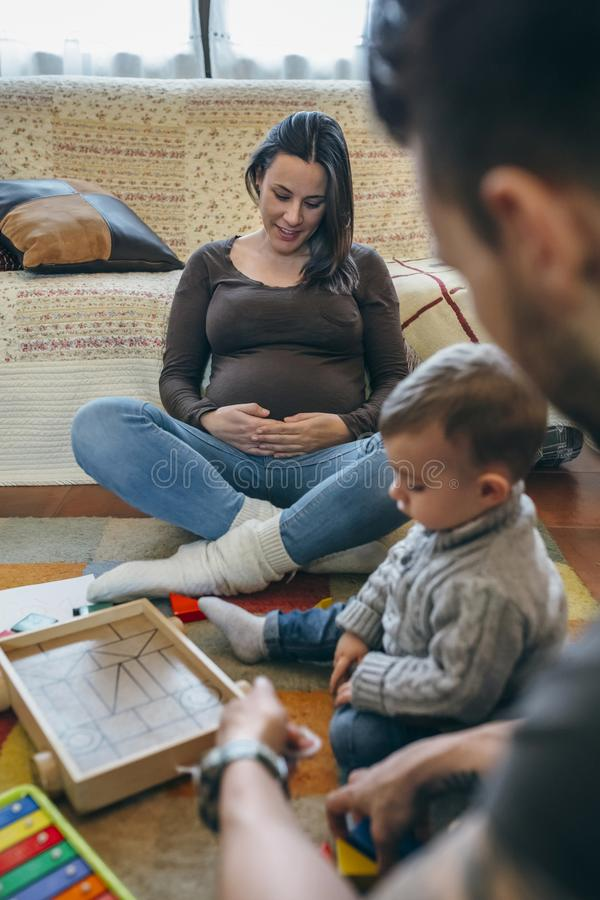 Engendre jugar con el niño mientras que la madre está mirando su vientre fotografía de archivo libre de regalías