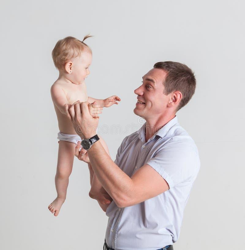 Engendre jugar con su hija que la detiene en sus brazos foto de archivo libre de regalías
