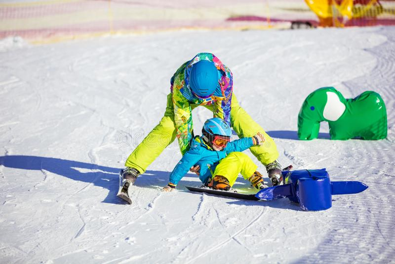 Engendre la ayuda consiguen poco en pies después de caída en cuesta del esquí imagen de archivo
