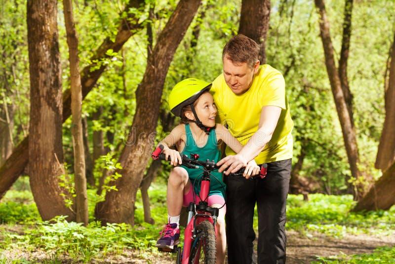 Engendre la ayuda de su hija montar la bicicleta foto de archivo libre de regalías