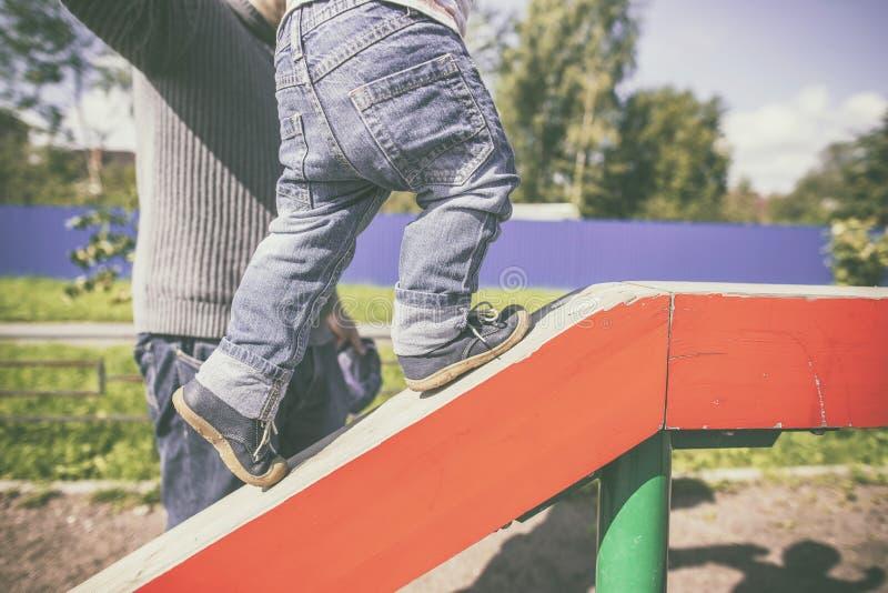 Engendre la ayuda de un niño subir para arriba el registro de madera foto de archivo