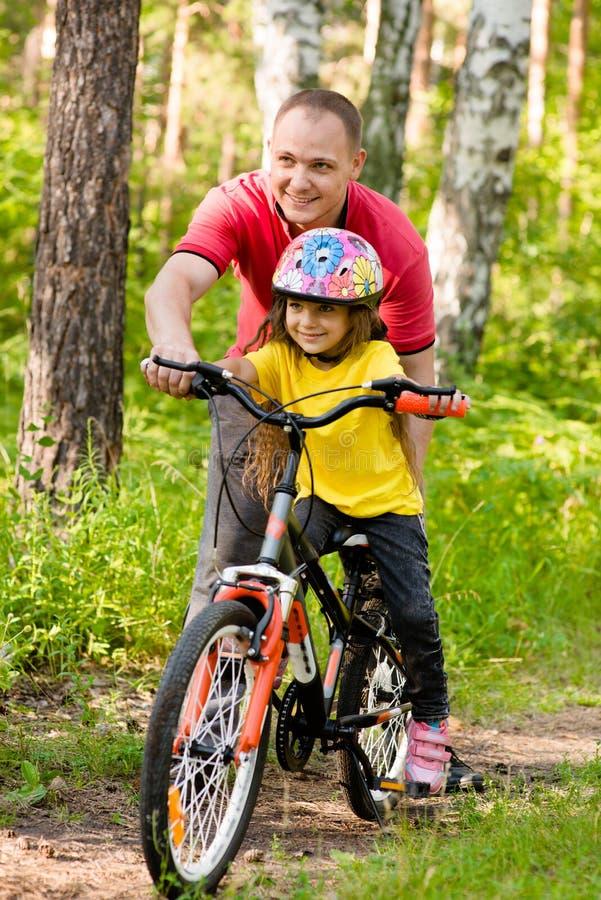 Engendre la enseñanza de su hija montar una bici imagen de archivo