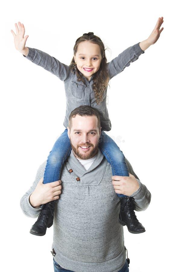 Engendre a la hija que lleva en sus hombros, tiro del estudio fotos de archivo libres de regalías