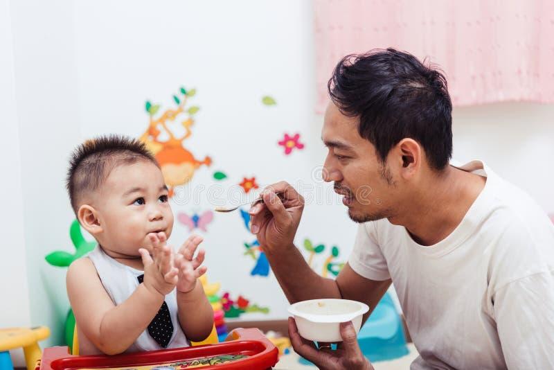 Engendre a la mamá temporaria que alimenta a su bebé del hijo de 1 año en silla foto de archivo