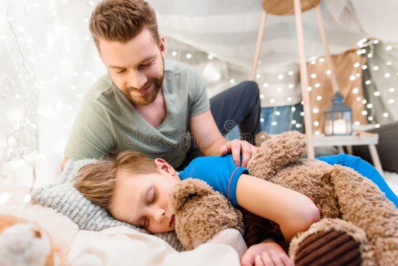 Engendre la mirada del pequeño hijo lindo que duerme con el oso de peluche foto de archivo libre de regalías