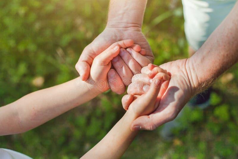 Engendre llevar a cabo las manos del niño, del padre y del niño imagen de archivo libre de regalías