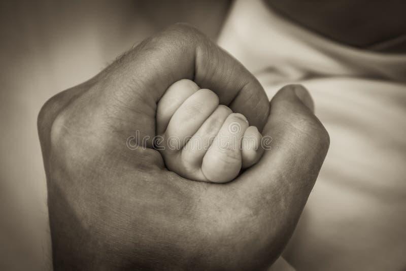 Engendre llevar a cabo su mano recién nacida del bebé en el puño que simboliza amor y cuidado fotografía de archivo