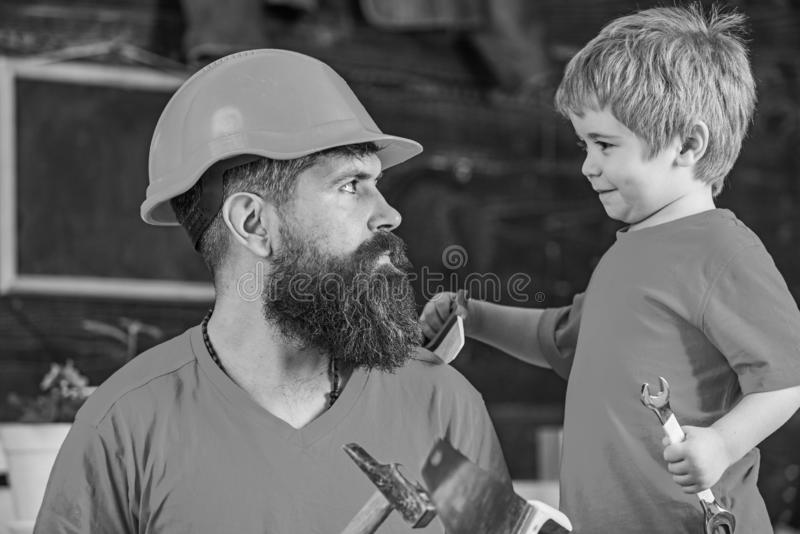Engendre, parent con la barba en el casco protector que enseña al pequeño hijo a utilizar diversas herramientas en taller de la e foto de archivo libre de regalías