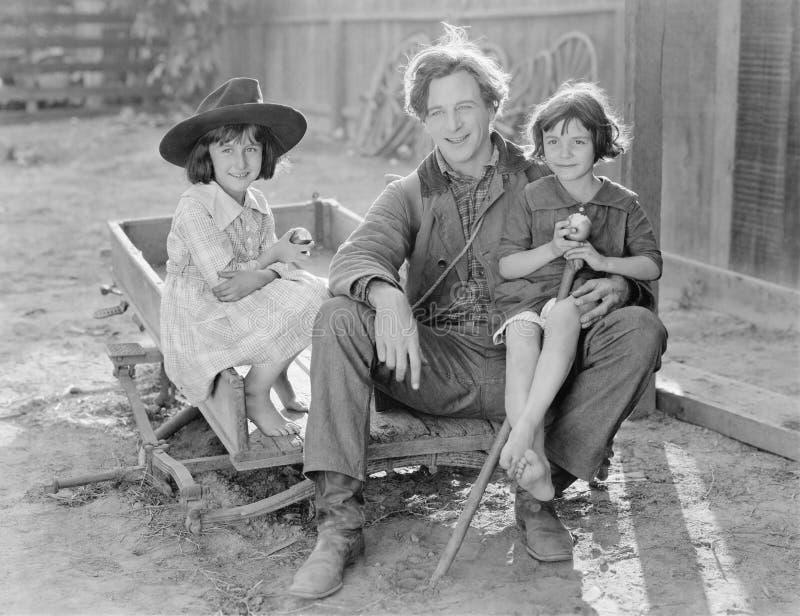 Engendre sentarse con sus dos hijas en un pequeño carro en una granja (todas las personas representadas no son vivas más largo y  foto de archivo