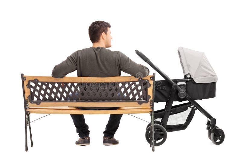 Engendre sentarse en banco con un cochecito de bebé foto de archivo libre de regalías