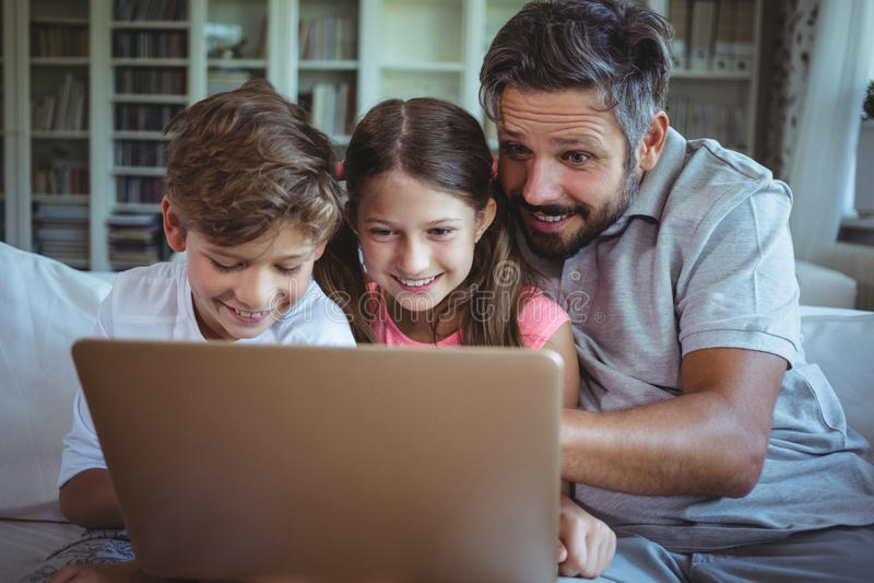 Engendre sentarse en el sofá con sus niños y usar el ordenador portátil en sala de estar foto de archivo libre de regalías