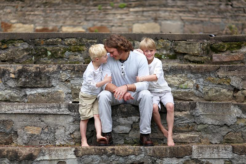 Engendre a Sitting con sus dos hijos jovenes afuera imagenes de archivo