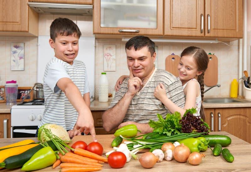 Engendre y dos niños en el interior casero de la cocina Familia, muchacha feliz y muchacho divirtiéndose con las frutas y verdura foto de archivo libre de regalías