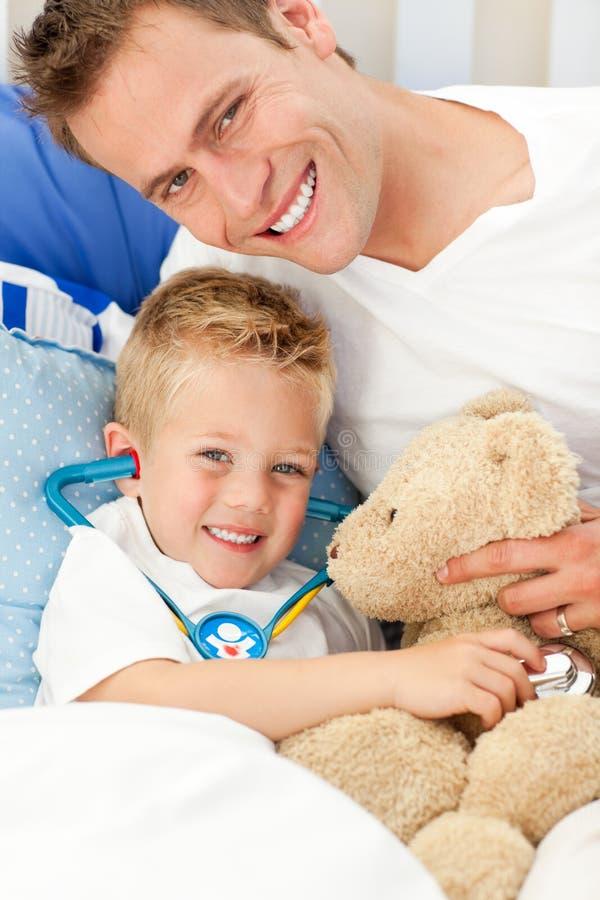 Engendre y su hijo enfermo que juega con un estetoscopio fotos de archivo libres de regalías