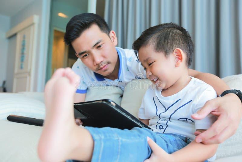Engendre y su hijo joven que se divierte por juego en una tableta fotografía de archivo