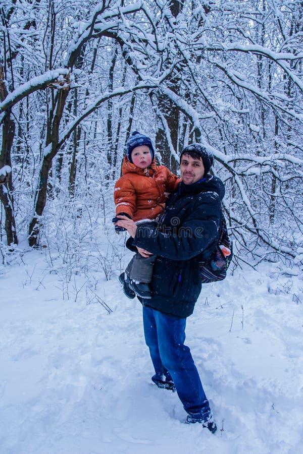 Engendre y su hijo que juega afuera, bosque del invierno en el fondo, nevando, feliz y alegre imagen de archivo