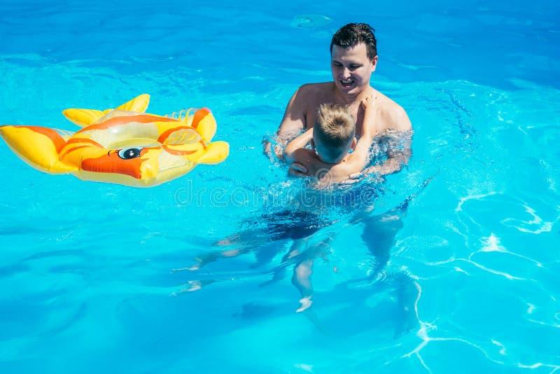Engendre y su hijo que se divierte en la piscina fotografía de archivo