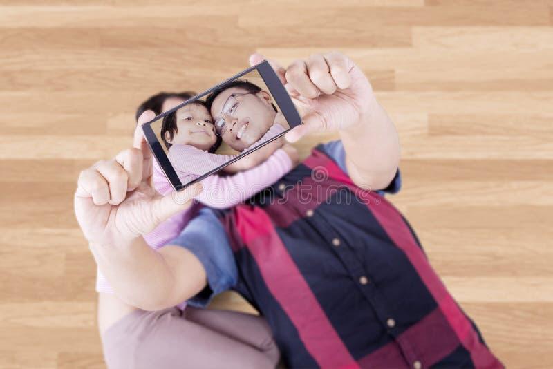 Engendre y su niño que toma la foto en el piso fotos de archivo