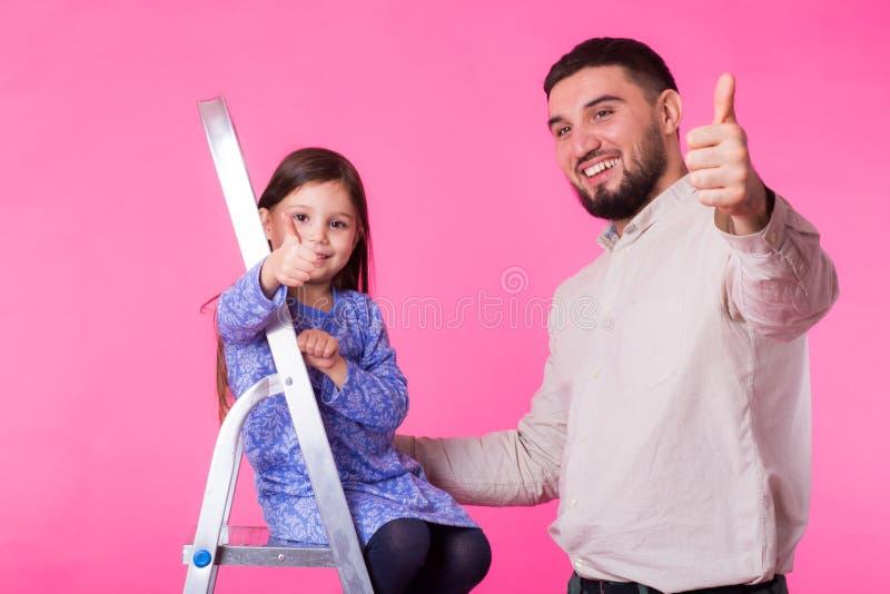 Engendre y su pequeña hija con los pulgares para arriba sobre fondo rosado El hombre y el bebé adultos son felices imagenes de archivo