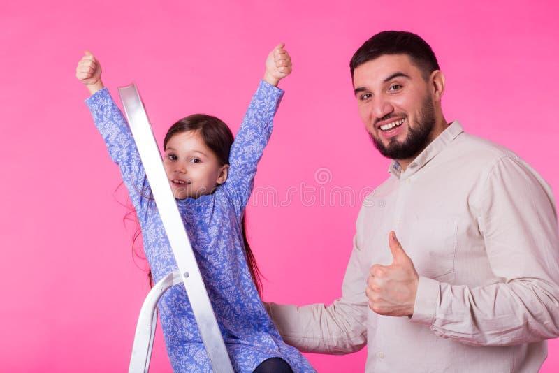 Engendre y su pequeña hija con los pulgares para arriba sobre fondo rosado El hombre y el bebé adultos son felices foto de archivo libre de regalías