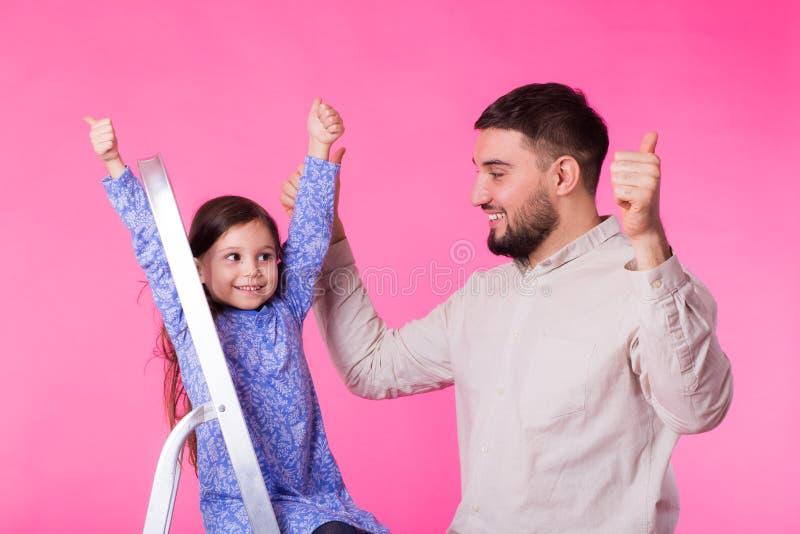 Engendre y su pequeña hija con los pulgares para arriba sobre fondo rosado El hombre y el bebé adultos son felices fotografía de archivo