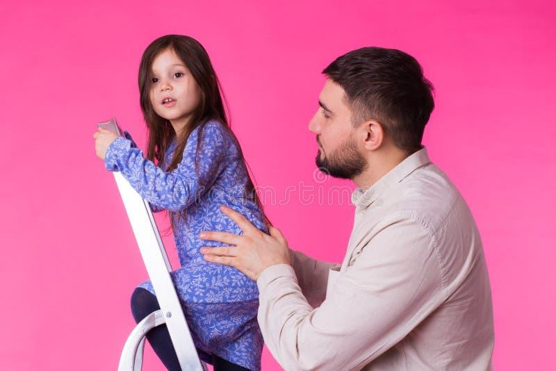 Engendre y su pequeña hija sobre fondo rosado El hombre y el bebé adultos son felices foto de archivo libre de regalías