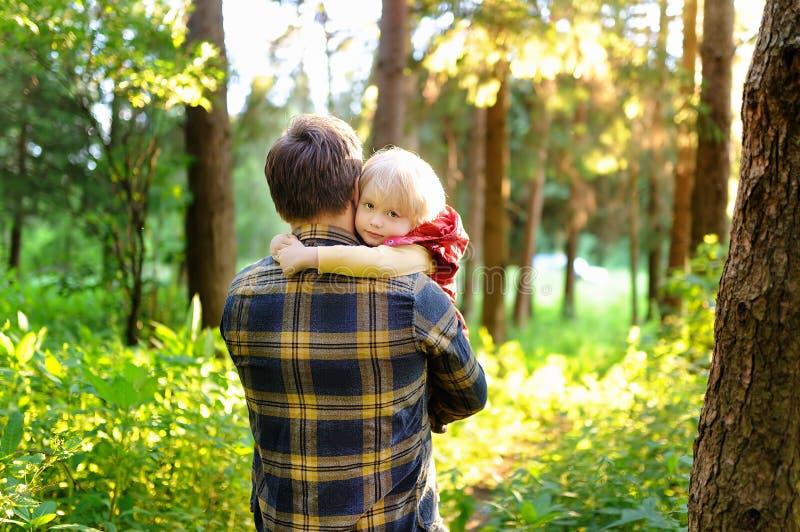 Engendre y su pequeño hijo durante las actividades que caminan en bosque en la puesta del sol imágenes de archivo libres de regalías