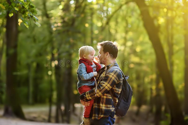 Engendre y su pequeño hijo durante las actividades que caminan en bosque en la puesta del sol foto de archivo