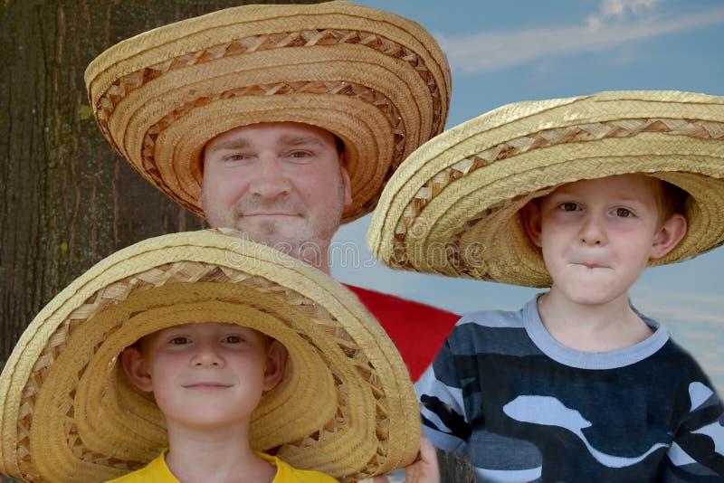 Engendre y sus dos hijos con los sombreros de paja mexicanos grandes imagen de archivo