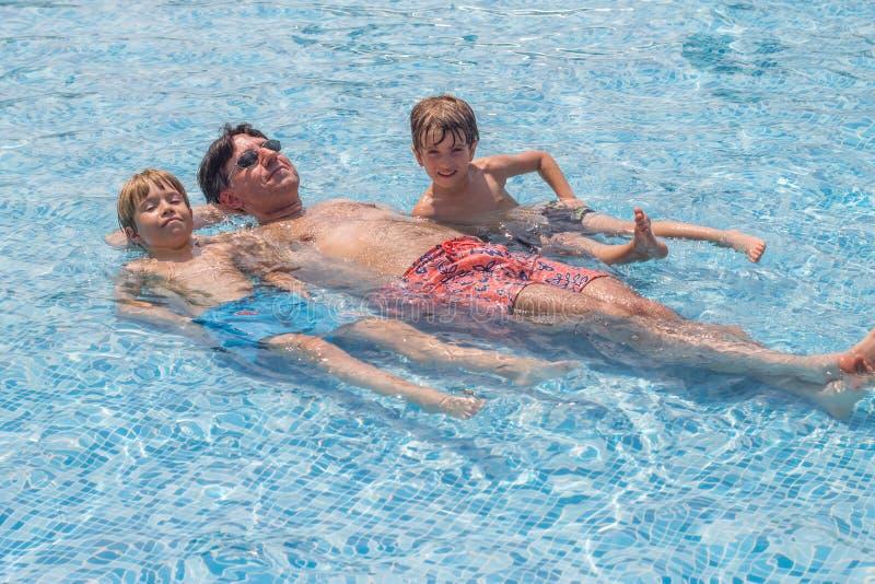 Engendre y sus muchachos que ponen en una piscina fotos de archivo