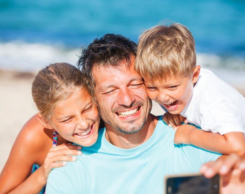 Engendre y sus niños en la playa que toma el selfie foto de archivo libre de regalías