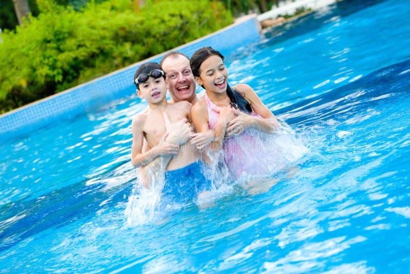Engendrez avec des enfants appréciant la piscine photos stock