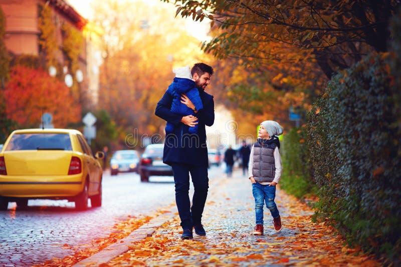 Engendrez avec des enfants marchant le long de la rue de ville d'automne photos stock