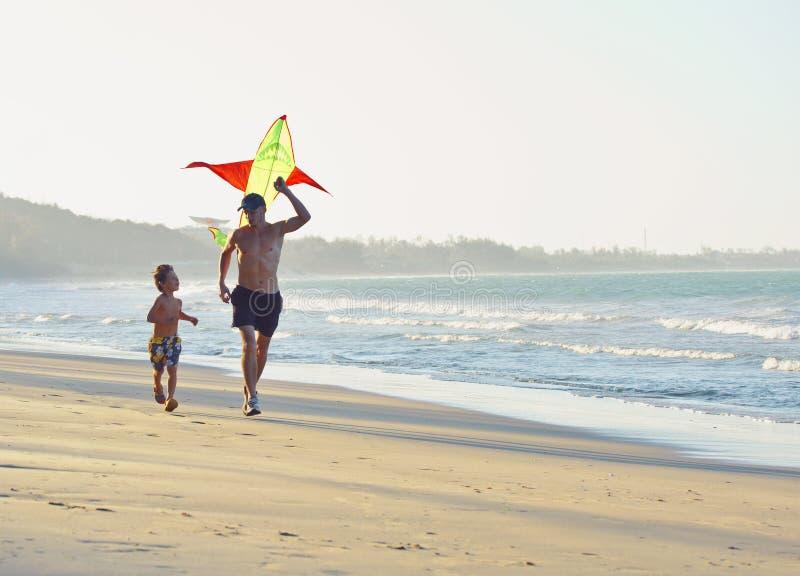 Engendrez avec le fils, coucher du soleil au littoral jouant le cerf-volant, famille heureuse image libre de droits